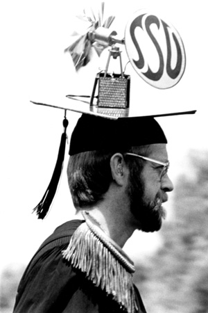 Man in graduate robes, his mortarboard has a miniature windmill