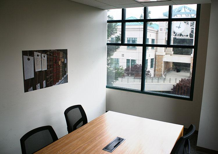 Unoccupied study room with a window, desk and 2 chairs.