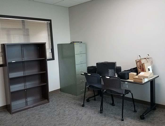 View of the VITaL lab, one desk with VR equipment, bookcase and file cabinet.