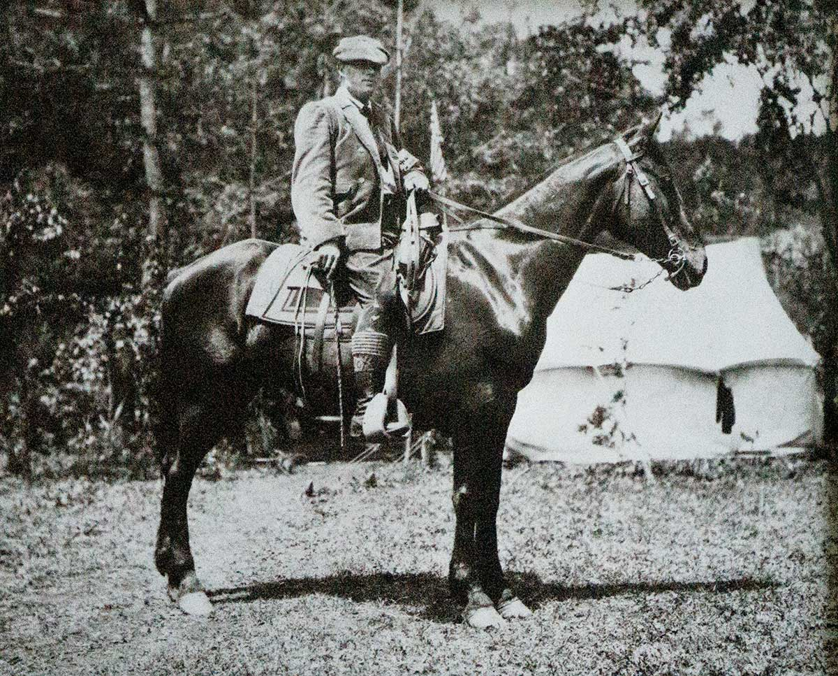 A man rides a horse.  They are facing the right.