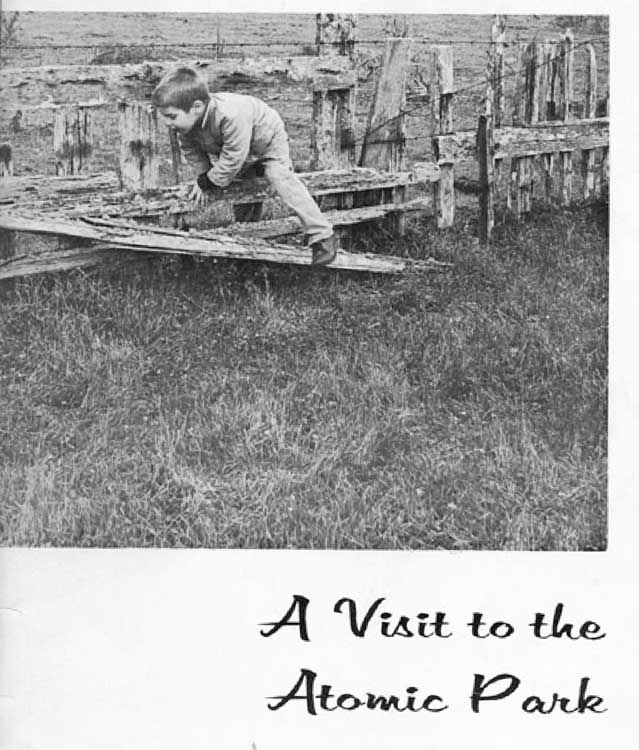 Young boy climbing a wooden fence.  Text is A Visit to the Atomic Park.