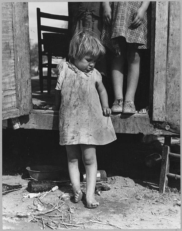 Young girl, barefoot and in a dirty dress.
