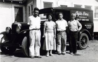 4 people stand in front of a car.