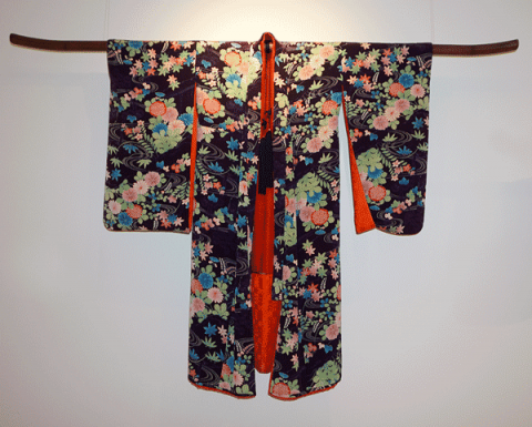 Kimono displayed on a wall.  Black background with flowers of green, pink and blue.  The inside of the kimono is red.