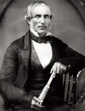 Portrait of a man sitting in a chair.