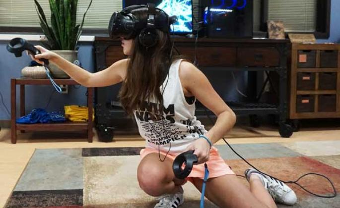 A woman is using VR equiptment, one arm extended.