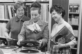 Librarians using a record player