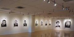 2 well lighted walls, with black and white photographs.