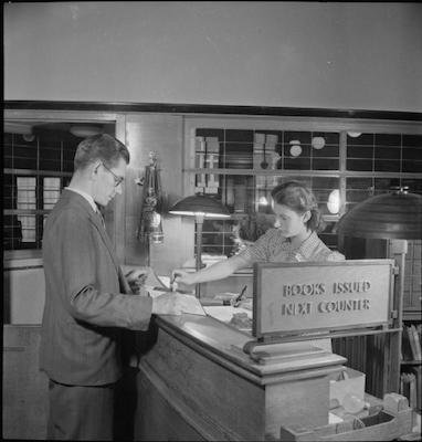Woman behind the desk in a library stamping a book for a male patron in a suit