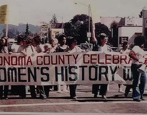 Women in a parade with a banner Sonoma County Celebrates Women's History.