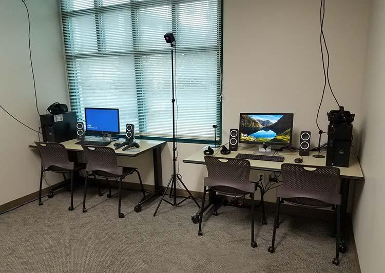 2 desks, each has a computer, and VR equipment.