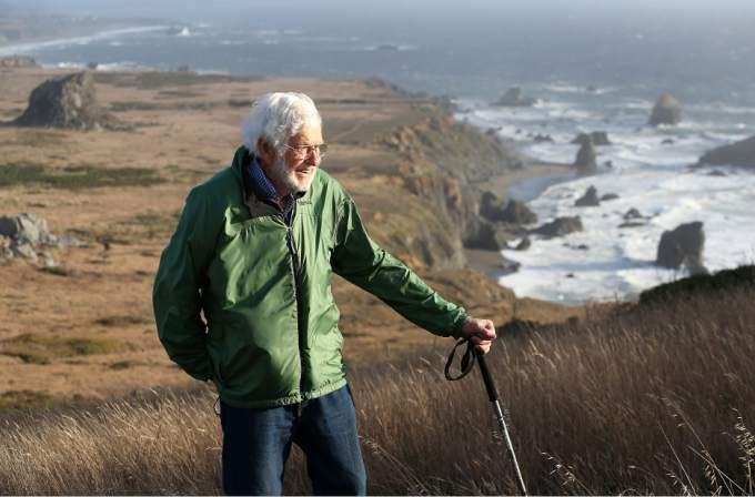 A man in a green jacket hiking along the California coast.