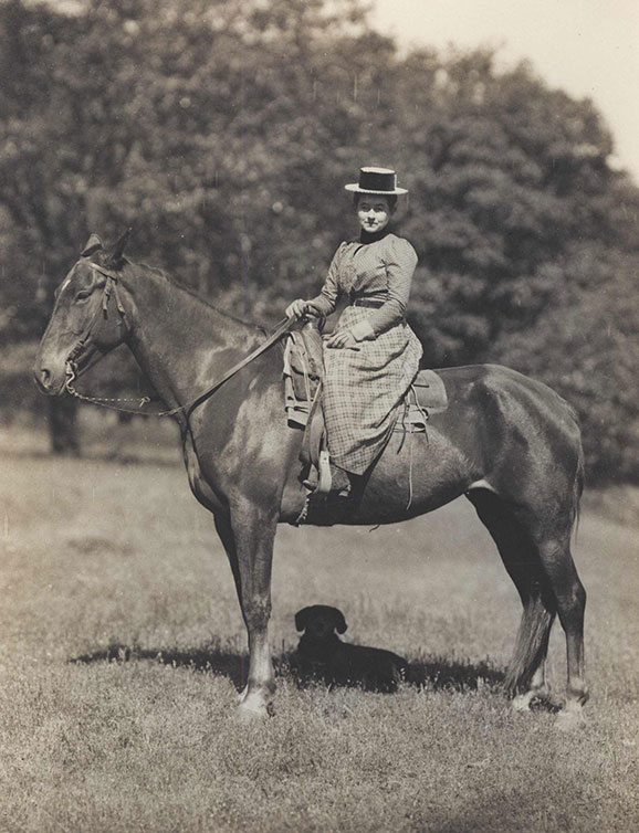 Woman on a horse.  She is dressed in turn of the 20th century clothes.