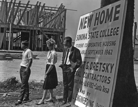 3 people looking at the construction of a Sonoma State building.