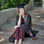Woman sitting on brick steps.  She is wearing a graduate gown.