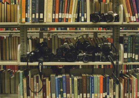 A metal bookshelf filled with film cameras