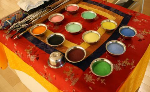 12 pot of different colored sand on a table.