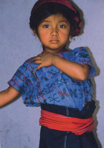A young girl with a blue shirt and earnings.