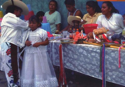 A woman wearing white pants with flowers braids a little girls hair while others watch.