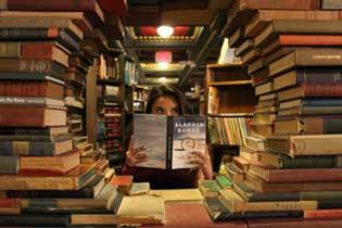 a woman is reading behind a circle of books.