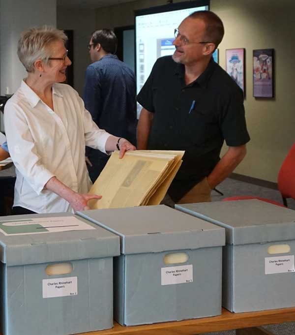 Woman and a man looking at archival documents.